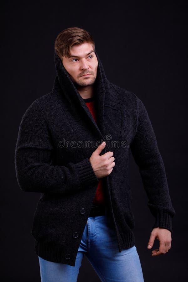 Stående av en ung man på en svart bakgrund som slås in i en kofta arkivfoton