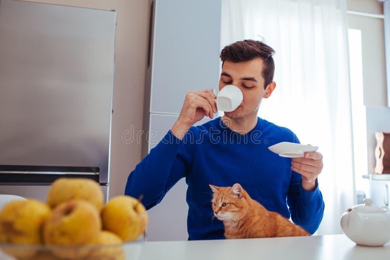 Stående av en ung man som dricker te med en katt på kök arkivfoton
