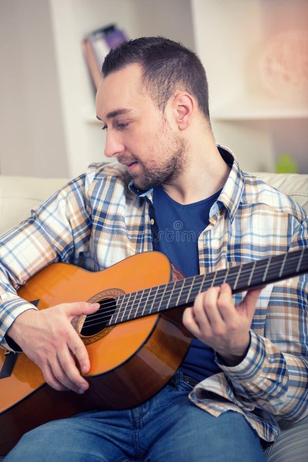 Stående av en ung man som spelar gitarren royaltyfri bild