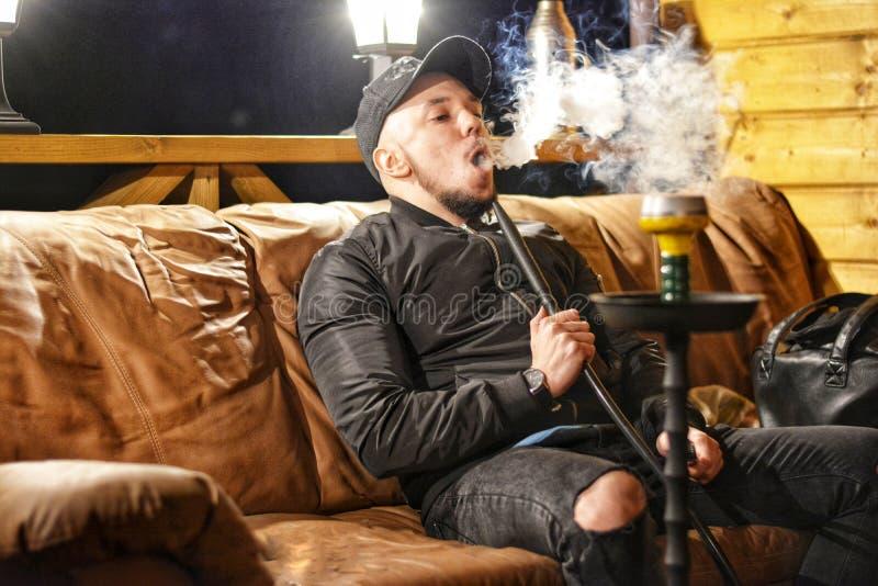 Stående av en ung man som utandas rök royaltyfri bild
