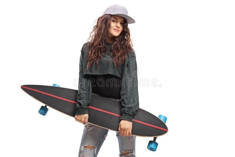 Stående av en ung moderiktig kvinnlig som rymmer en longboard royaltyfri foto
