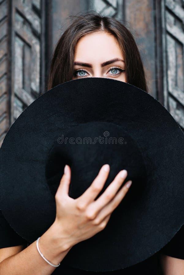 Stående av en ung nätt flicka med en svart hatt i henne armar arkivbilder