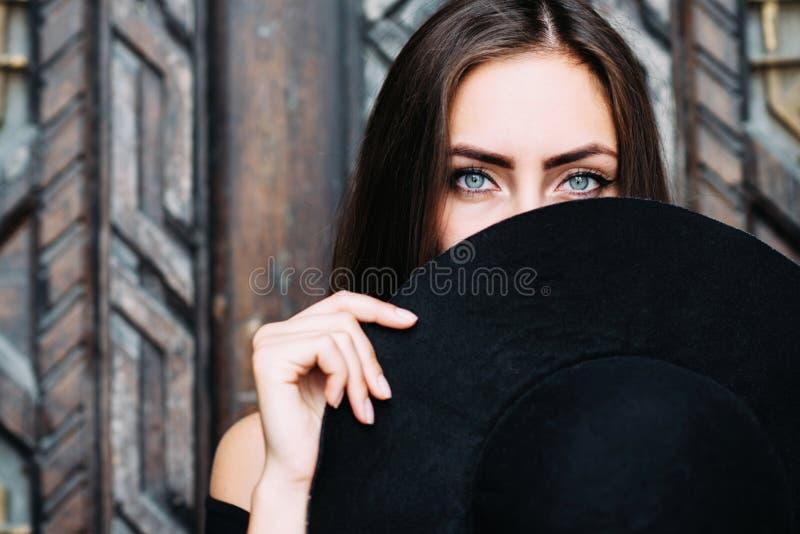 Stående av en ung nätt flicka med en svart hatt i henne armar arkivfoto