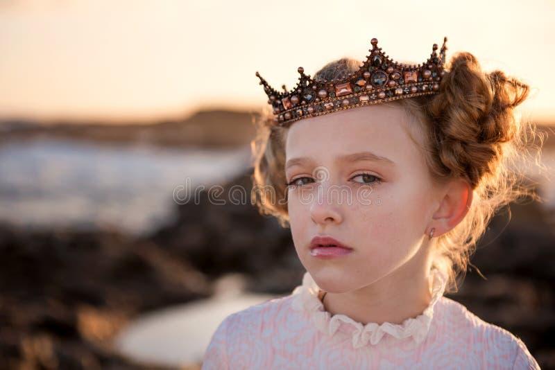 Stående av en ung nyckfull prinsessa i strålarna av resningsolen i kronan royaltyfria bilder