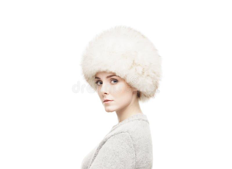 Stående av en ung och härlig kvinna i en vinterhatt som isoleras på vit arkivbilder