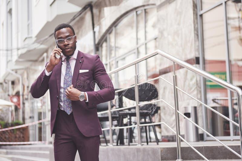 Stående av en ung och stilig afrikansk amerikanaffärsman som talar i en dräkt över telefonen arkivfoto