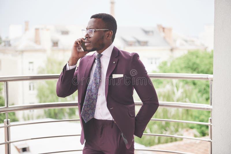 Stående av en ung och stilig afrikansk amerikanaffärsman som talar i en dräkt över telefonen arkivfoton