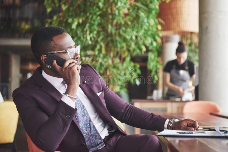 Stående av en ung och stilig afrikansk amerikanaffärsman som talar i en dräkt över telefonen Förbereda sig för en affär royaltyfria foton