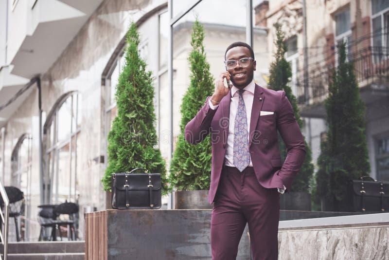 Stående av en ung och stilig afrikansk amerikanaffärsman som talar i en dräkt över telefonen Förbereda sig för en affär arkivbild