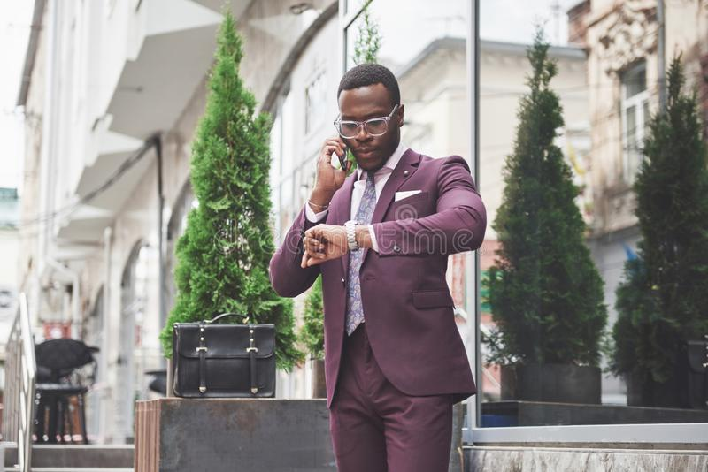 Stående av en ung och stilig afrikansk amerikanaffärsman som talar i en dräkt över telefonen Förbereda sig för en affär arkivfoto