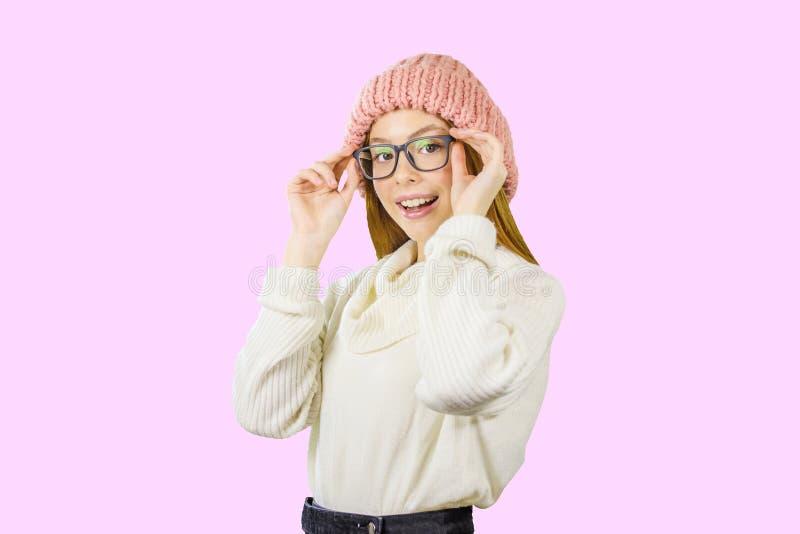 Stående av en ung rödhårig flicka i en stucken rosa hatt som rymmer exponeringsglas med båda händer som ler att se royaltyfri foto