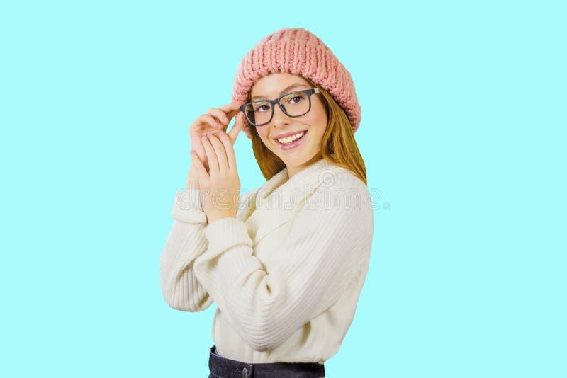 Stående av en ung rödhårig flicka i en stucken rosa hatt, som rymmer exponeringsglas med hennes hand som ler som ser royaltyfria bilder