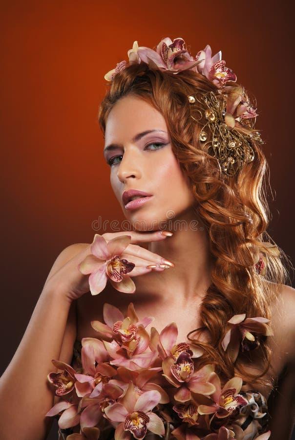 Stående av en ung redheadkvinna i härliga blommor royaltyfri foto
