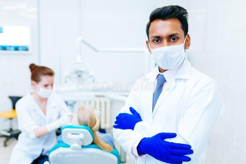 Stående av en ung säker asiatisk manlig tandläkare i klinik framme av wfemaletandläkaren som kontrollerar tänder till patienten t fotografering för bildbyråer