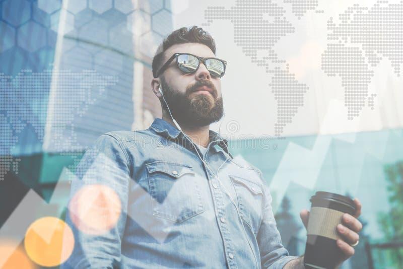 Stående av en ung skäggig affärsman i solglasögon och skjortan som står utomhus- hållande kopp kaffe royaltyfri foto