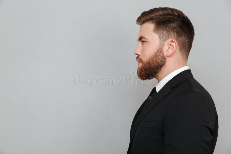 Stående av en ung skäggig man i dräkten som framåtriktat ser royaltyfria foton