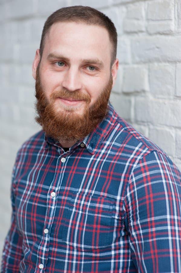 Stående av en ung skäggig man i en flanellskjorta royaltyfri bild