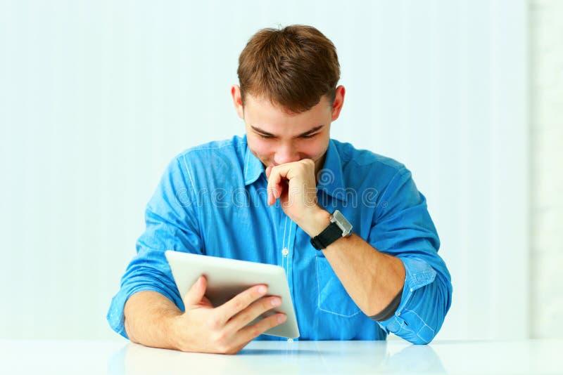 Stående av en ung skratta affärsman med minnestavladatoren royaltyfri bild