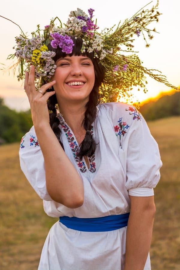 Stående av en ung skratta kvinna i en broderad lång vit fotografering för bildbyråer