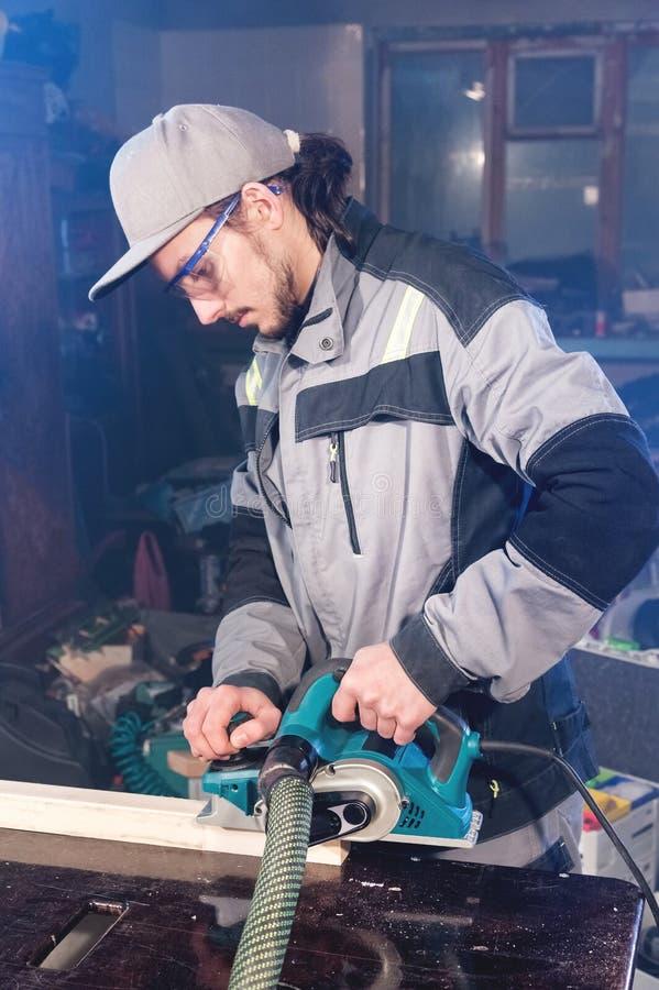 Stående av en ung snickare som arbetar med en elektrisk nivå i ett hem- träseminarium Begreppet av en affärsidé arkivfoton