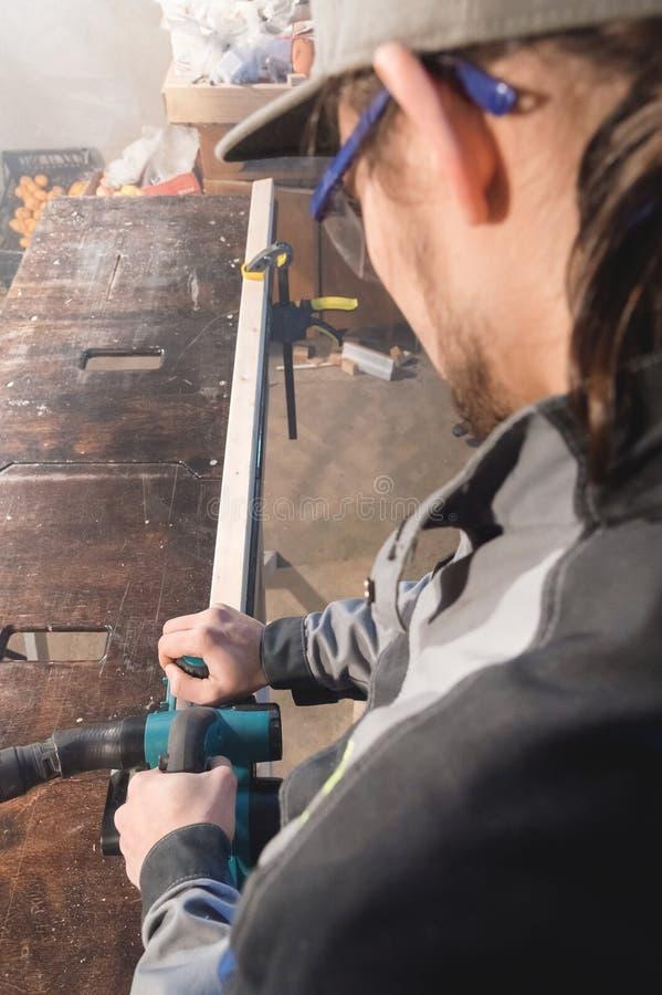 Stående av en ung snickare som arbetar med en elektrisk nivå i ett hem- träseminarium Begreppet av en affärsidé royaltyfri bild