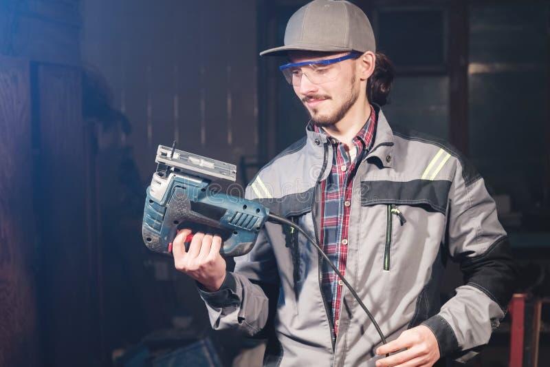 Stående av en ung snickareföreningsmänniska i overaller som bär ett lock och skyddsglasögon med en elektrisk figursåg i hand på e royaltyfri foto