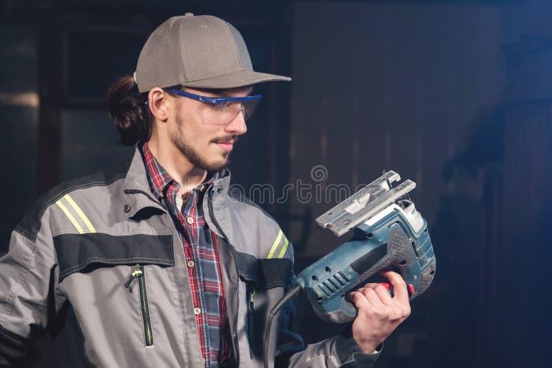 Stående av en ung snickareföreningsmänniska i overaller som bär ett lock och skyddsglasögon med en elektrisk figursåg i hand på e arkivfoton