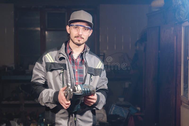 Stående av en ung snickareföreningsmänniska i overaller som bär ett lock och skyddsglasögon med en elektrisk figursåg i hand på e arkivbild