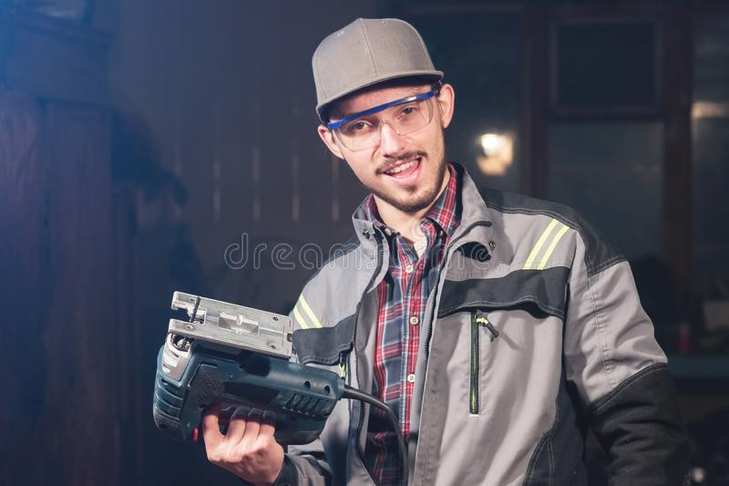 Stående av en ung snickareföreningsmänniska i overaller som bär ett lock och skyddsglasögon med en elektrisk figursåg i hand på e arkivfoto