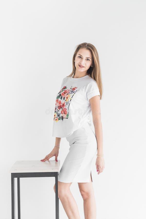 Stående av en ung stilfull brunettflicka som poserar för kameran på vit bakgrund royaltyfri foto