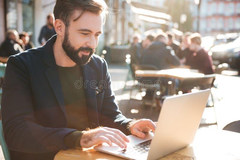 Stående av en ung stilfull man som arbetar på bärbar datordatoren arkivfoto