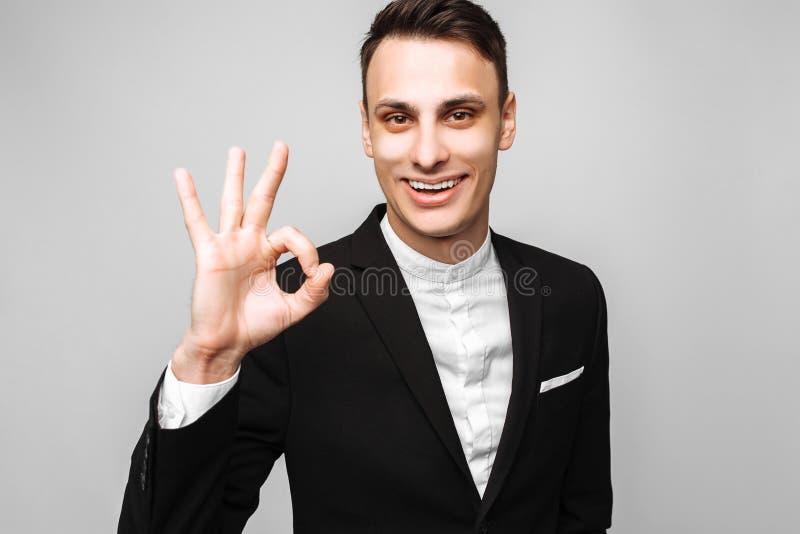 Stående av en ung stilig lycklig man, i en affärsdräkt, smil arkivfoto