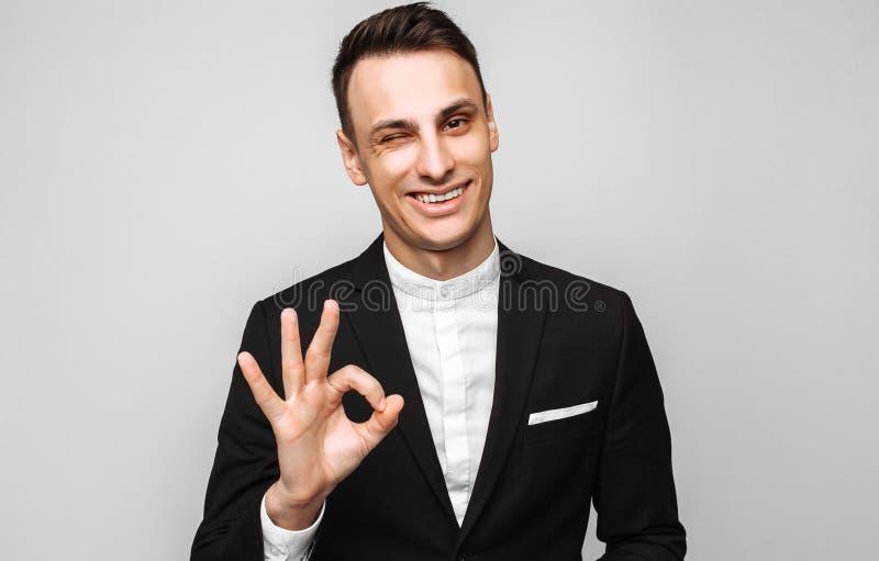 Stående av en ung stilig lycklig man, i en affärsdräkt, smil royaltyfri foto