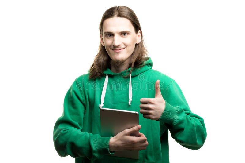 Stående av en ung stilig man i den gröna hoodien som ser kameran, rymmer en digital minnestavla i en hand och visar ok mest gest royaltyfri bild