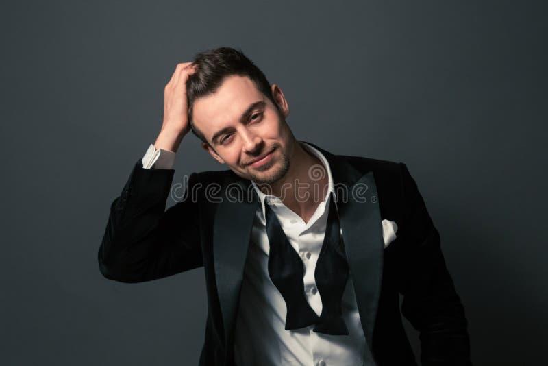 Stående av en ung stilig man i en dräkt-, fluga- och skjortabu arkivfoton
