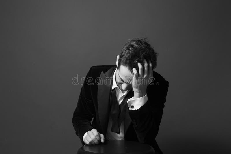 Stående av en ung stilig man i ett matställeomslag, fluga och royaltyfria foton