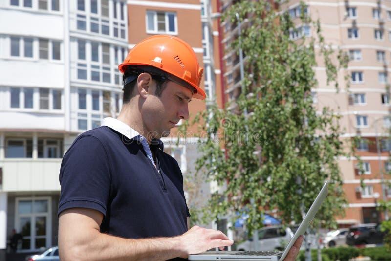 Stående av en ung stilig man i en skyddande hjälm med en bärbar dator i hans händer framme av en hög byggnad arkivbilder