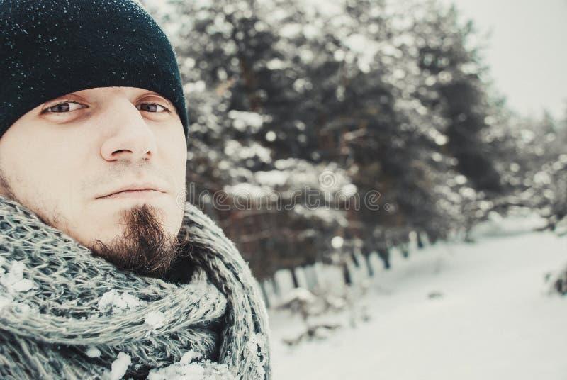 Stående av en ung stilig man med ett skägg livsstil för liggande för härliga flickahandskar grön över scarfsnowvinter royaltyfria bilder