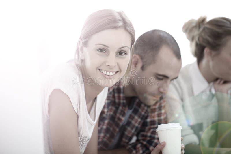 Stående av en ung studentflicka med vänner som dricker kaffe arkivbild