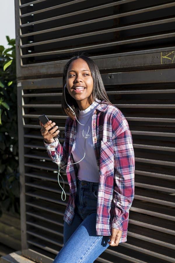 Stående av en ung svart kvinna som lyssnar till musik med hörlurar, medan luta på ett metalliskt staket arkivfoton