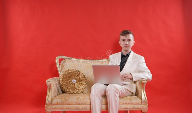 Stående av en ung tonårig dräkt och att sitta för kontor för man bärande vit på den guld- lyxiga soffan på röd bakgrund han arbet arkivfoton