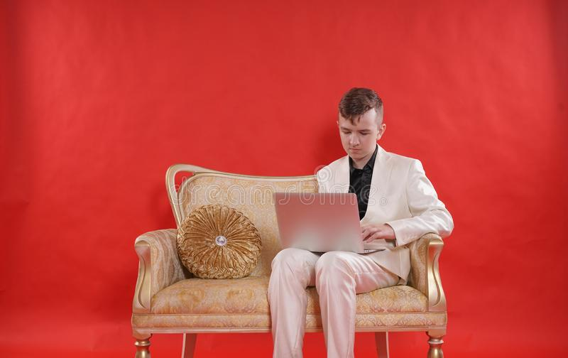 Stående av en ung tonårig dräkt och att sitta för kontor för man bärande vit på den guld- lyxiga soffan på röd bakgrund han arbet arkivfoto
