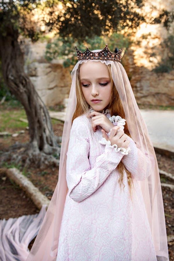 Stående av en ung trollkvinnaconcubine som står i en felik skog i en lång klänning och krona med en skyla och ser modestly ner arkivfoton
