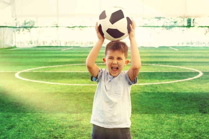 Stående av en ung unge för skola för fotbollspelare på fotbollfältet som ropar och lyfter bollen över hans huvud arkivbilder