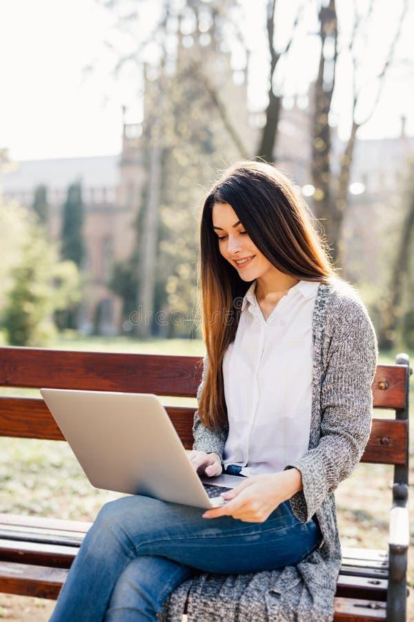 Stående av en ung yrkesmässig kvinna som använder en bärbar datordator, medan sitta på en bänk i en parkera, på en solig dag royaltyfri foto