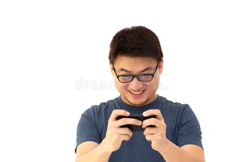 Stående av en upphetsad asiatisk man i mörkt - blå t-skjorta och bärande exponeringsglas som spelar lekar på mobiltelefonen royaltyfria foton