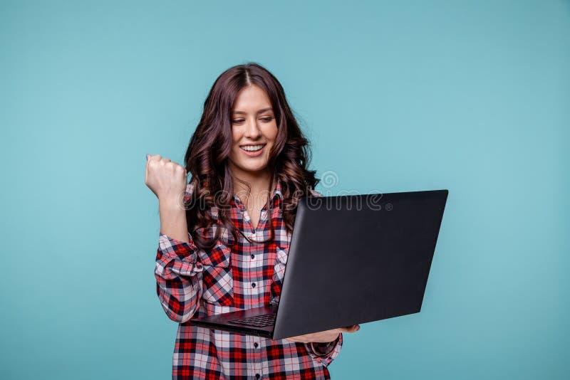 Stående av en upphetsad framgång för dator och för fira för ung flickainnehavbärbar dator som isoleras över blått royaltyfri fotografi