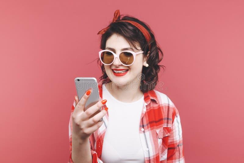 Stående av en upphetsad härlig flicka som bär den röda skjortan som rymmer mobiltelefonen isolerad över rosa bakgrund arkivfoton