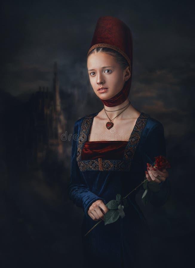 Stående av en ursnygg flicka i medeltida eraklänning och huvudbonad Medaljong i en form av hjärta Hållande röd ros i händer arkivbilder