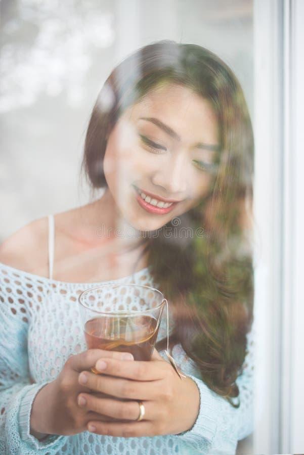 Stående av en ursnygg ung asiatisk kvinna som kopplar av med koppen av ho fotografering för bildbyråer
